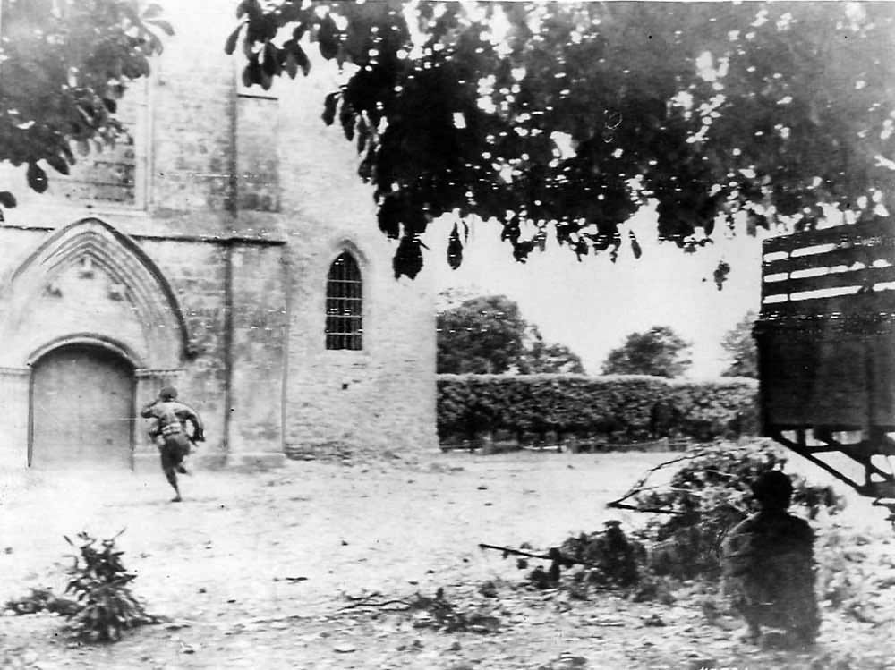 Airborne Trooper runs for sniper hiding in Church in St. Mere Eglise