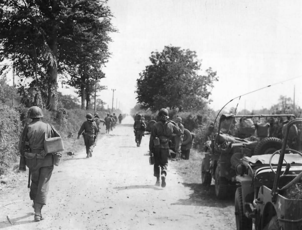 American Soldiers Advancing Past Jeeps on Road to Cherbourg France 30 June 1944
