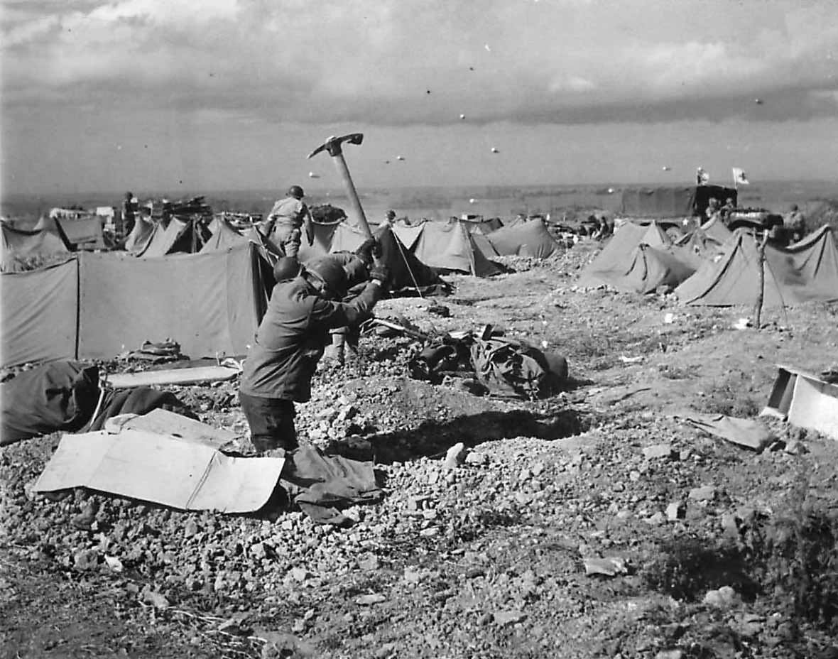 Barrage balloons overhead as US Medics dig in on D-Day beach