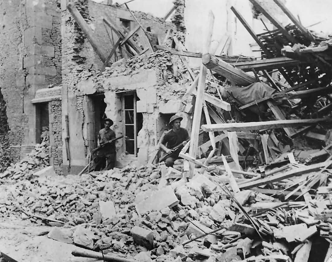 British Troops Advance through Ruins of Demeuville Normandy 1944