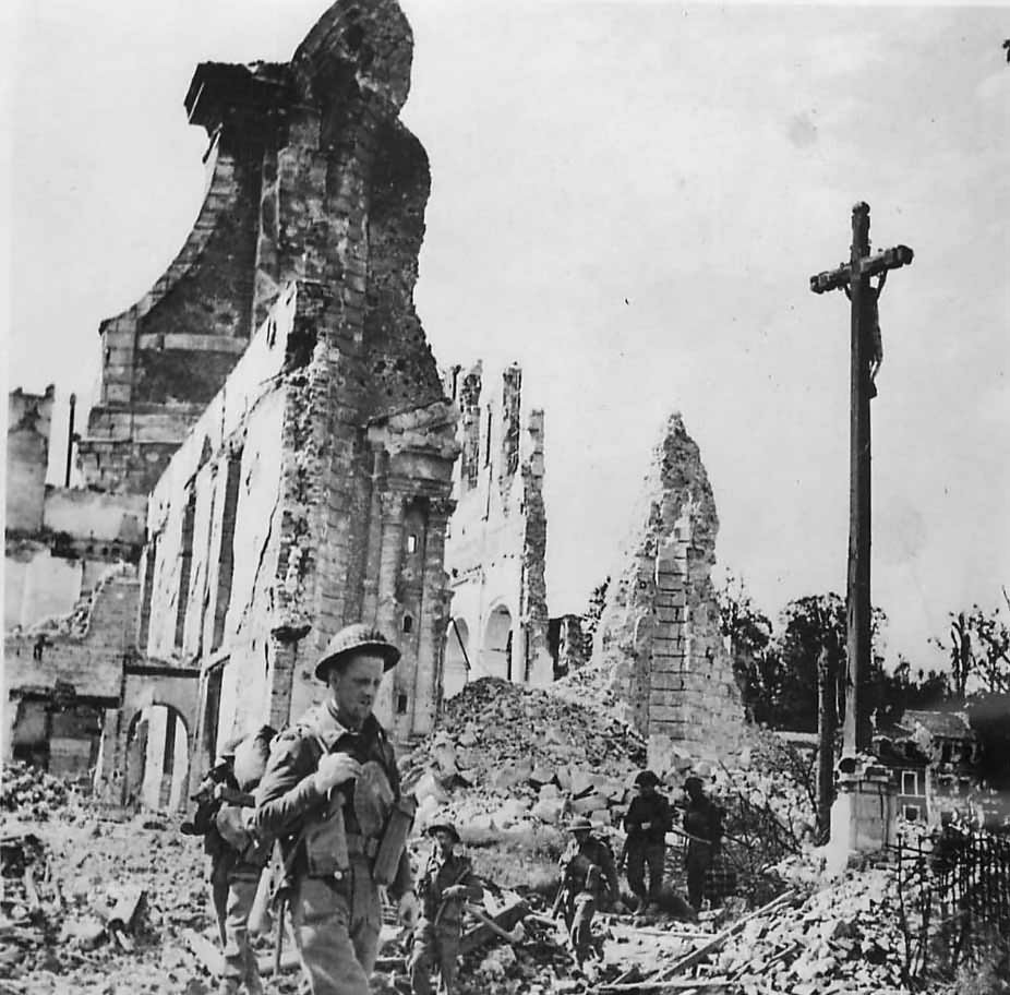 British soldiers pass ruins of St. Desir Church in Lisieux Normandy