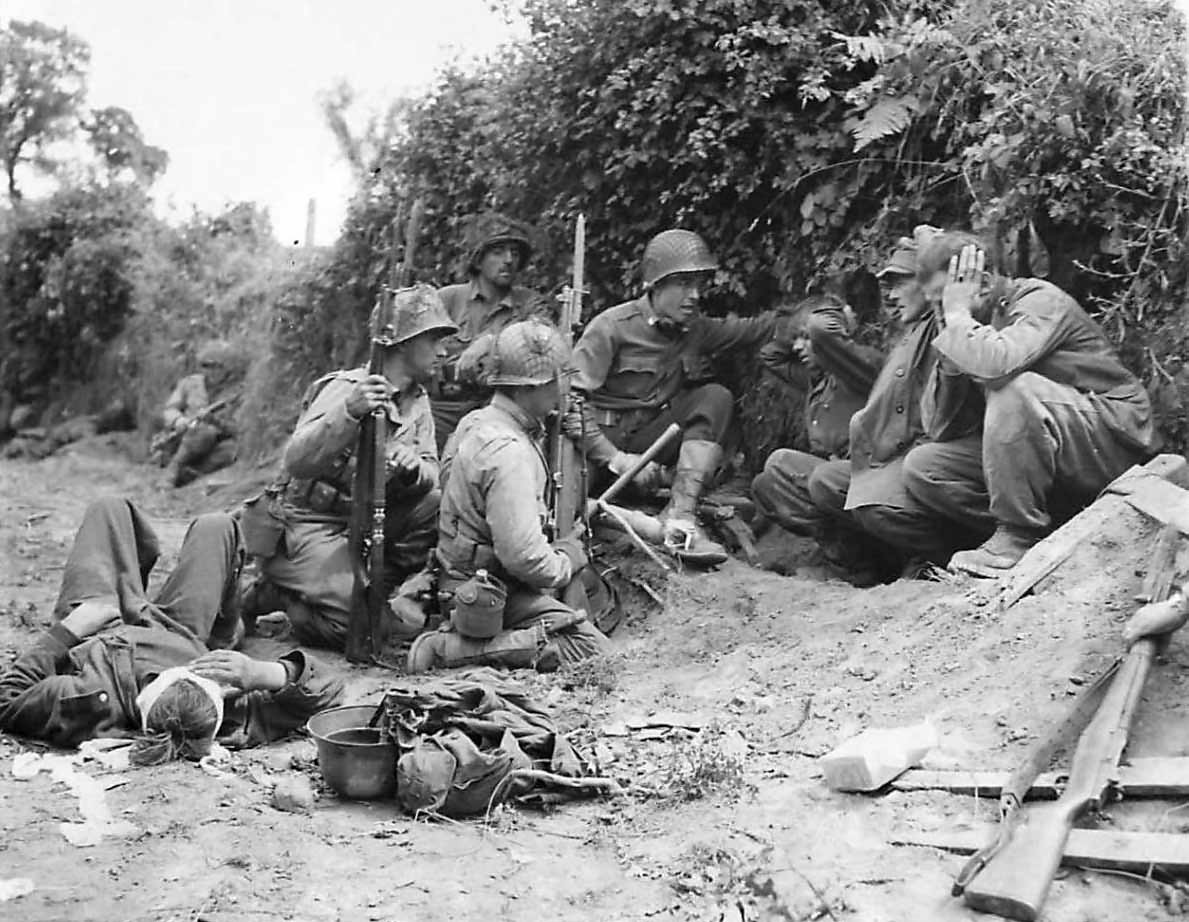 Captured German soldiers shelter with US soldiers at St. Lo July 1944