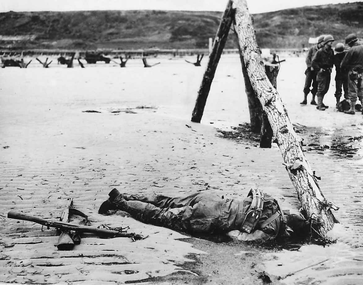 Crossed rifles beside fallen US soldier on D-Day Omaha Beach