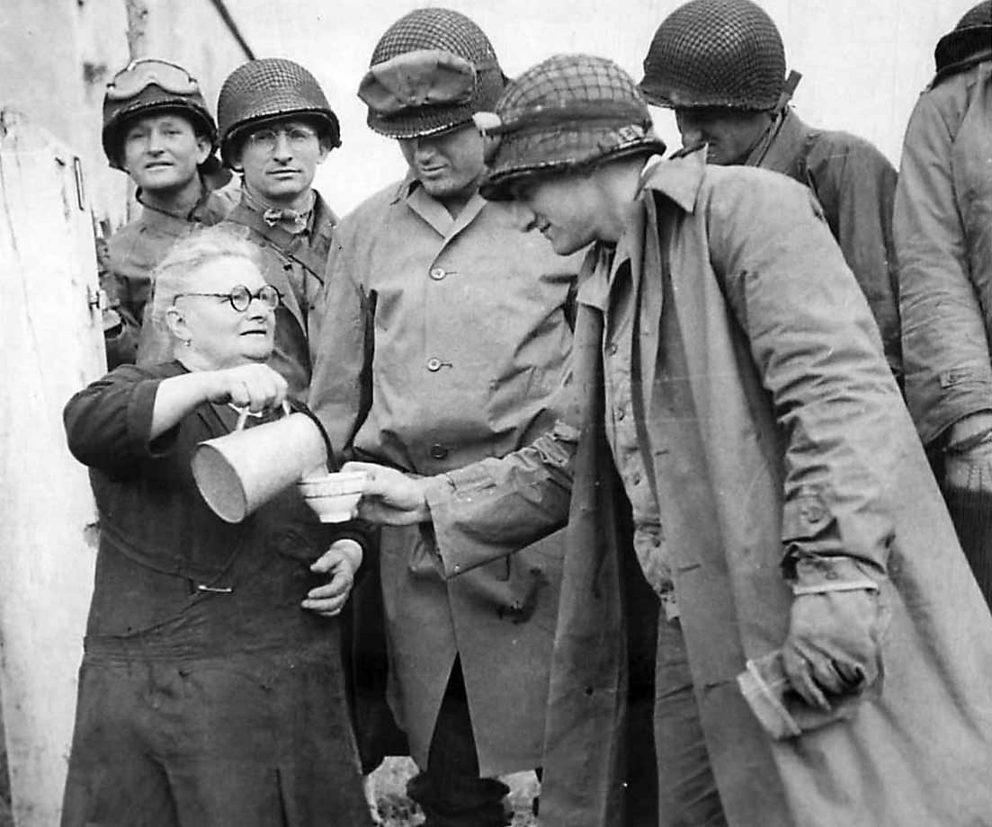 Elderly woman pours milk for US Army soldiers in the Normandy area of France