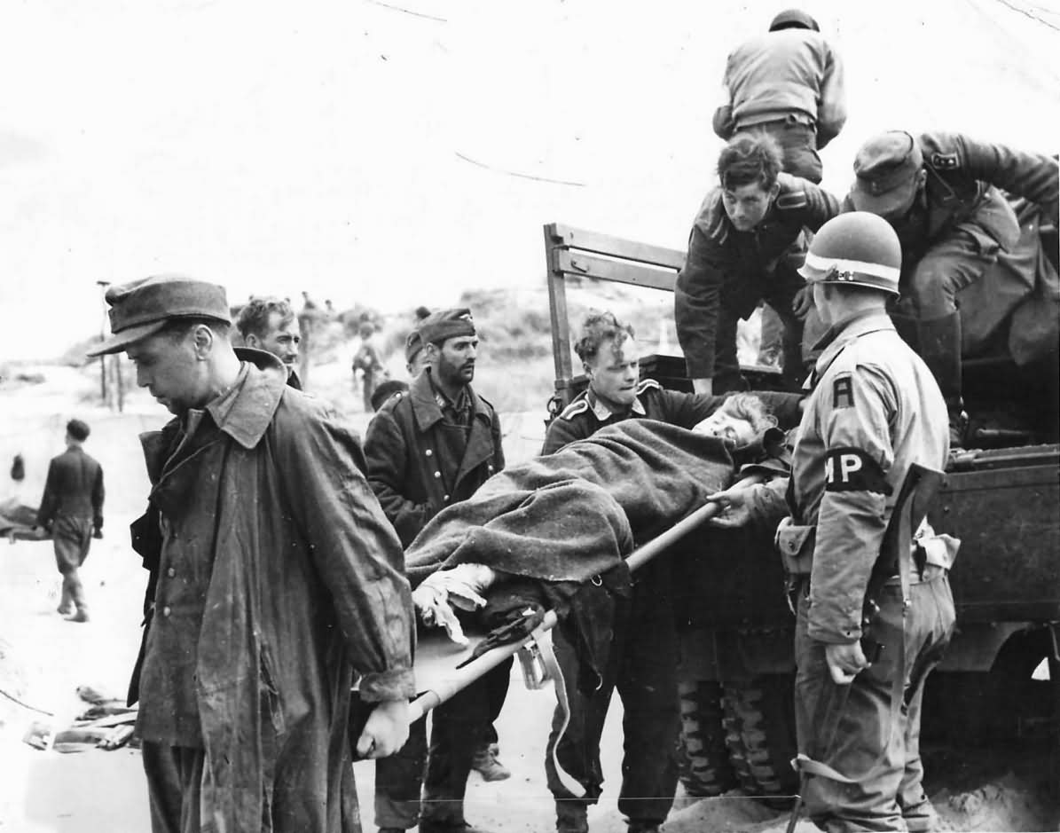 German Prisoners Unload Wounded Comrade on Normandy Beachhead 1944