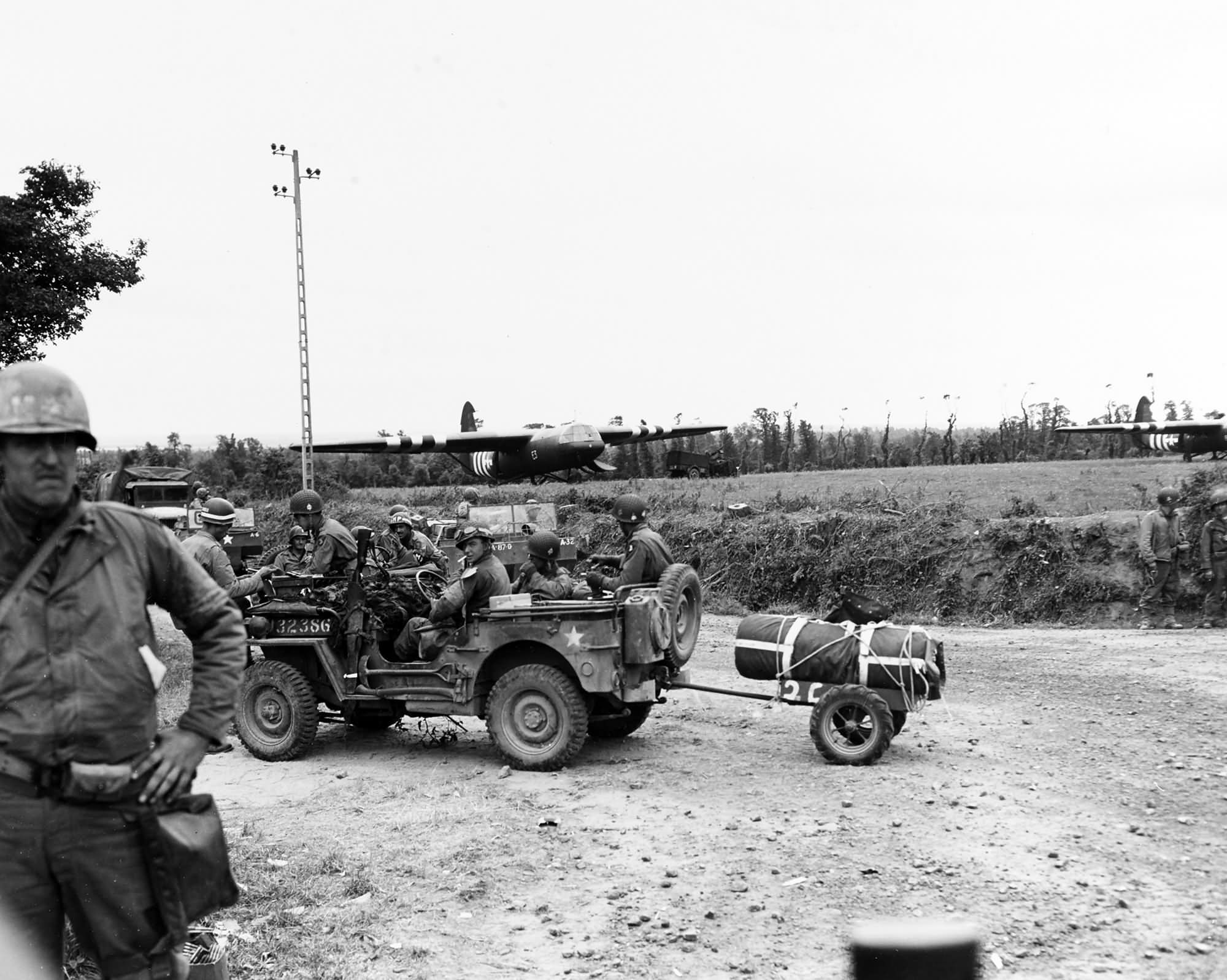 Infantrymen in Jeep get directions from a MP at a Normandy crossroads