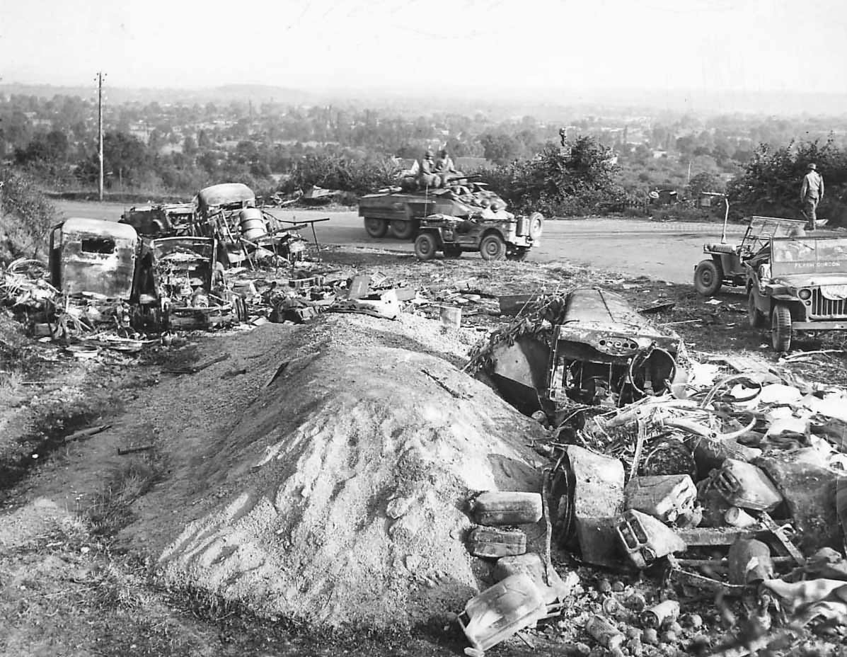M8 and Jeep passing wrecked German vehicles in Avranches