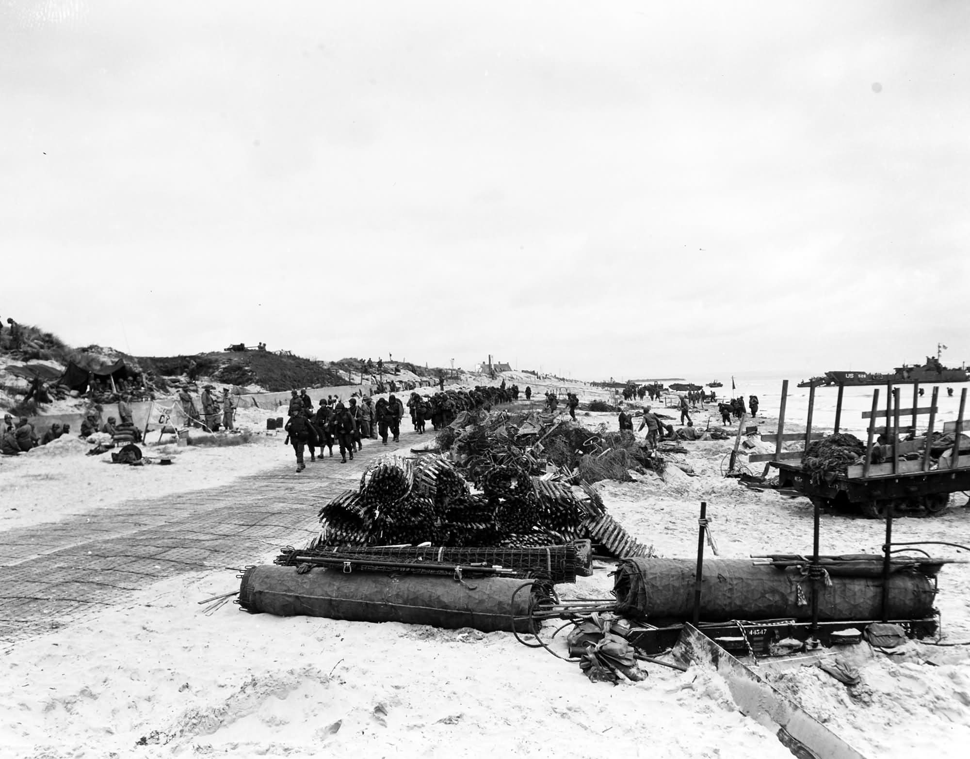 Scene on Utah Beach with troops marching up the road 9 June 1944