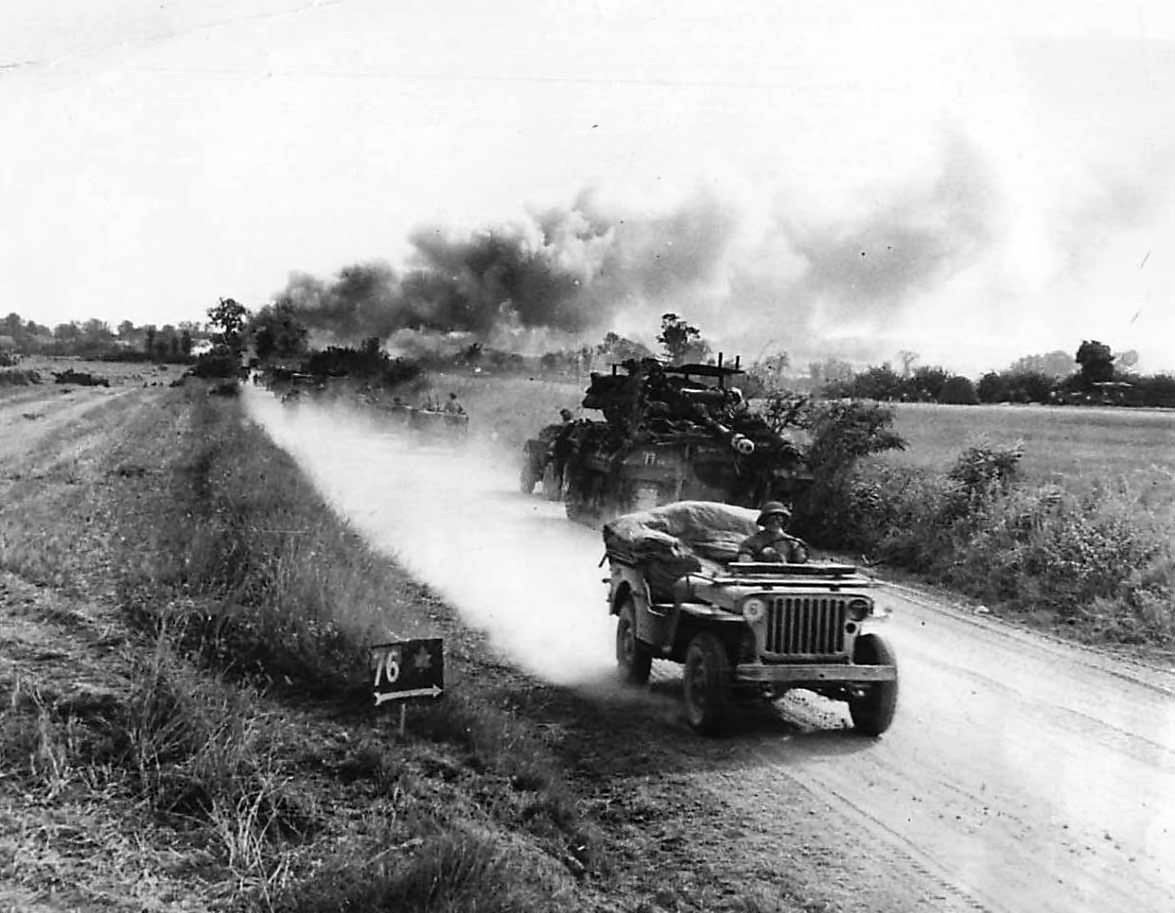 Troops pass burning German equipment on road to combat zone Falaise, Summer 1944