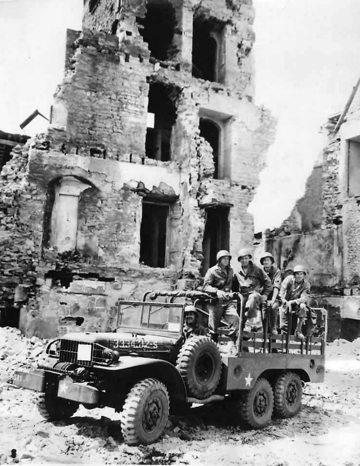 Troops and Dodge WC63 truck amid ruins of Trevieres 1944