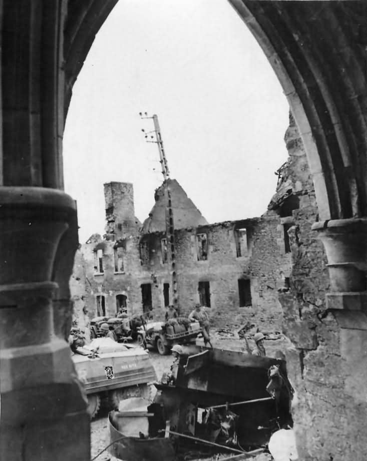 US Army Soldiers and Vehicles Move through St. Giles Normandy France July 1944