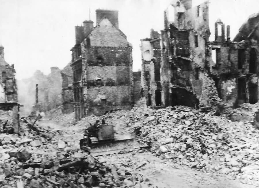 US Army engineers use bulldozer to force a path through street in war shattered Valognes Normady France 1944