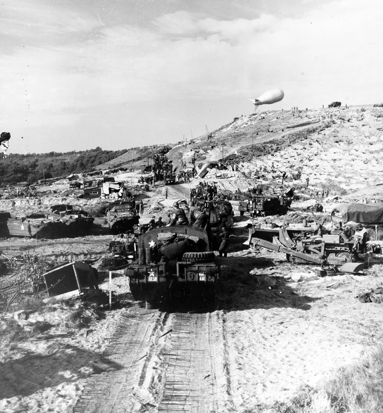 US Army vehicles move inland from a Normandy invasion beach
