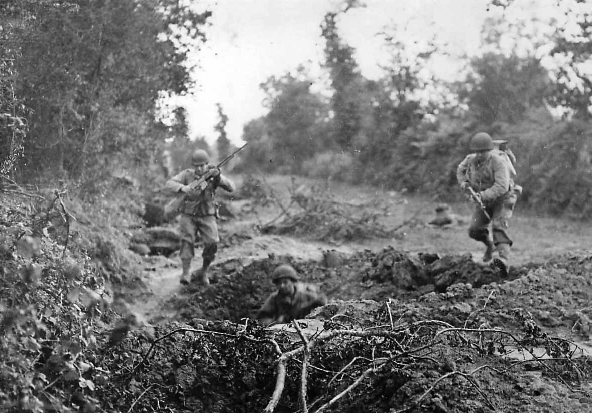 US Infantrymen leap for safety of shell hole in Normandy