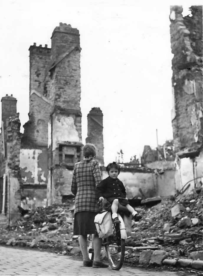 Woman and child on bicycle inspect ruins of Mortain