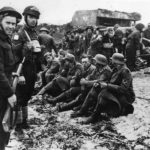 Canadian troops guard German POW on D-Days Juno Beach