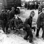 German POW carry wounded comrades to landing craft on a Normandy beach