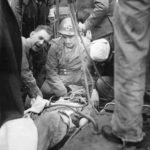 Medics transferring wounded soldier from D-Day beachhead