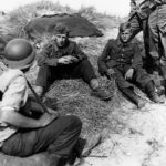 Polish prisoner in German uniform is interrogated by US soldiers 15 June 1944