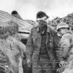 Wounded German Prisoner with MP of 1st ESB 449th MP Co in Normandy