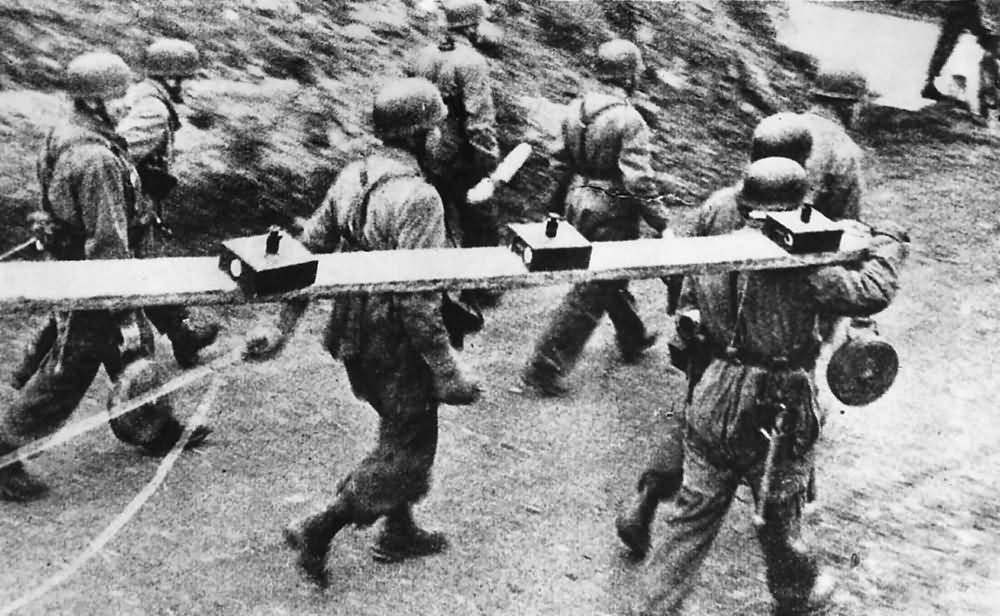 Fallschirmjagers of 1 Fallschirmjagerdivision carry wooden boxed land mines for planting near the Nettuno area of the Anzio beachhead 1944