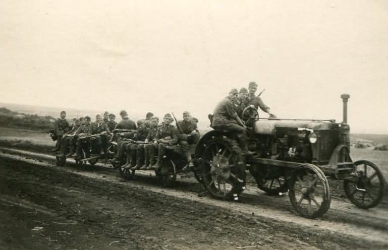Wehrmacht soldiers riding on a tractor