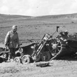 US soldier examines the wreckage of a Panzer III which was ko in battle at Kasserine Pass 1943