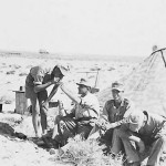 Afrika korps soldiers in desert by camo tent