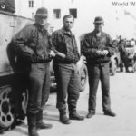 Waffen-SS soldiers posing beside a Sd.Kfz 11