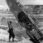 Seabee Inspects Wing of Wrecked A6M Zero at Munda Airport