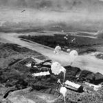 Parachute bombs are dropping from low-flying American planes on revetments protecting dispersed G4M bombers
