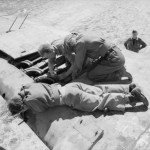Armourers of No. 89 Squadron RAF installing a 0.303 Browning machine gun in the wing of a Bristol Beaufighter Mk VIF at Castel Benito Libya