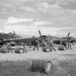 Ground crew rolling drums of petrol to Hurricane Mk IV of No 6 Squadron RAF at Araxos Greece