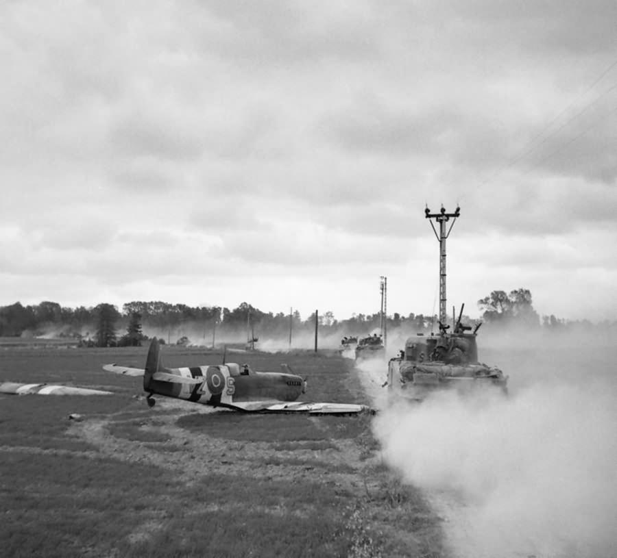 Sherman tanks move up past a crash landed Spitfire, for an attack on Tilly-sur-Seulles, Normandy 17 June 1944