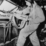 Waist gunner readying his M2 Browning machine gun aboard Boeing B-17