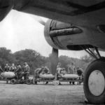 Pilot chalks message on bomb as crewmen load B-17, England 1942