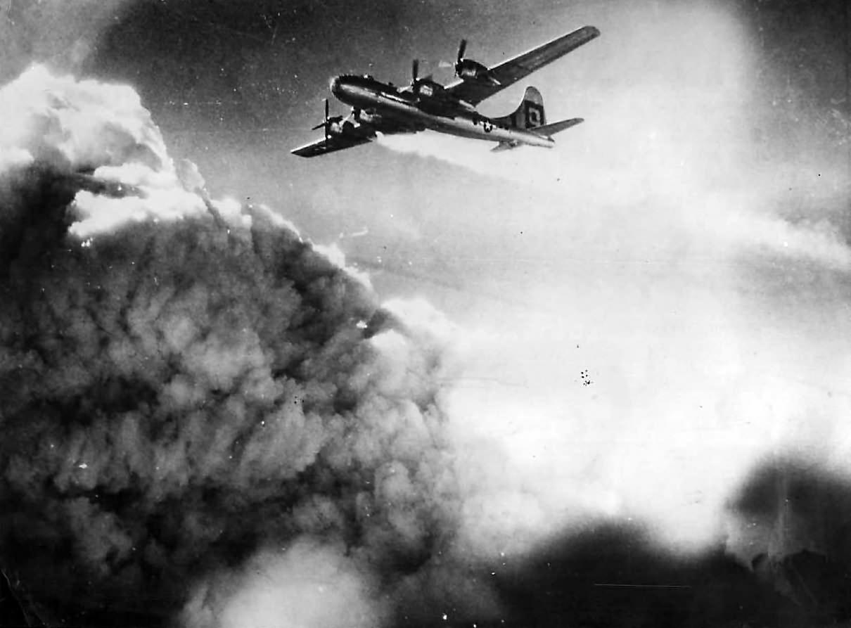 Flames trail engine of B-29 over Kobe, July 1945