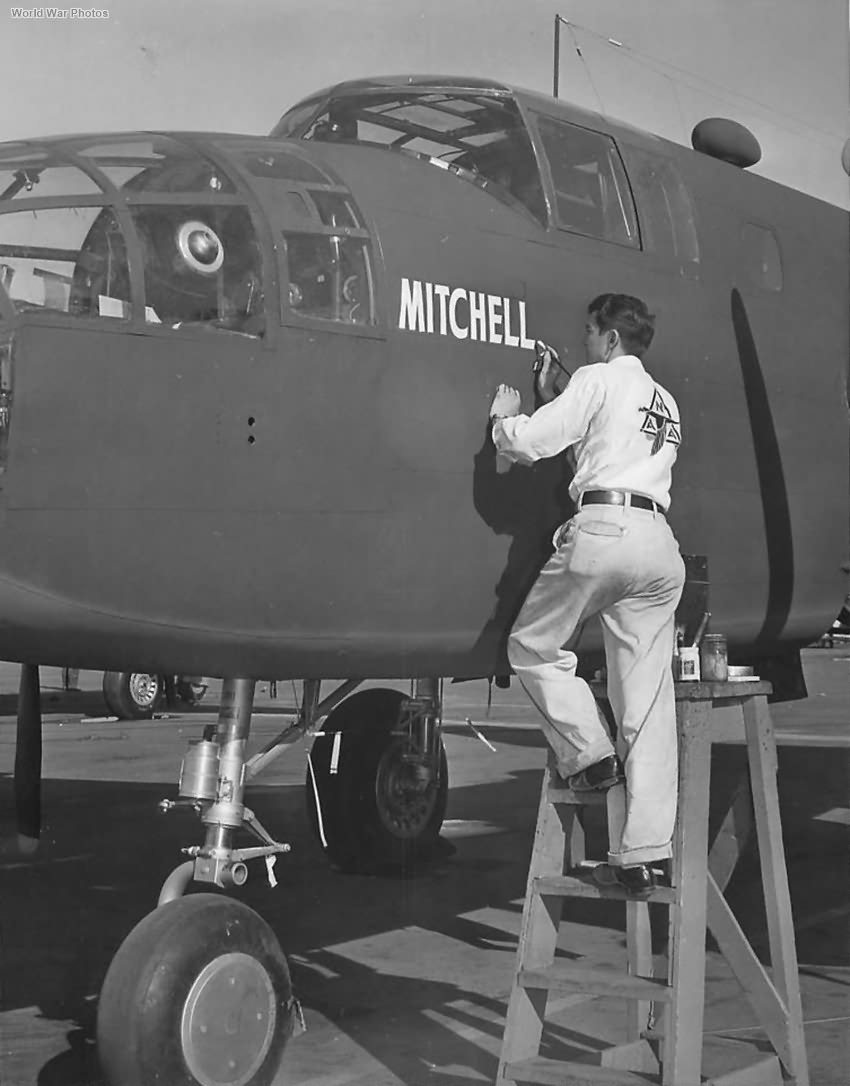Workman at NAA factory in Inglewood painting General Mitchell's name on B-25