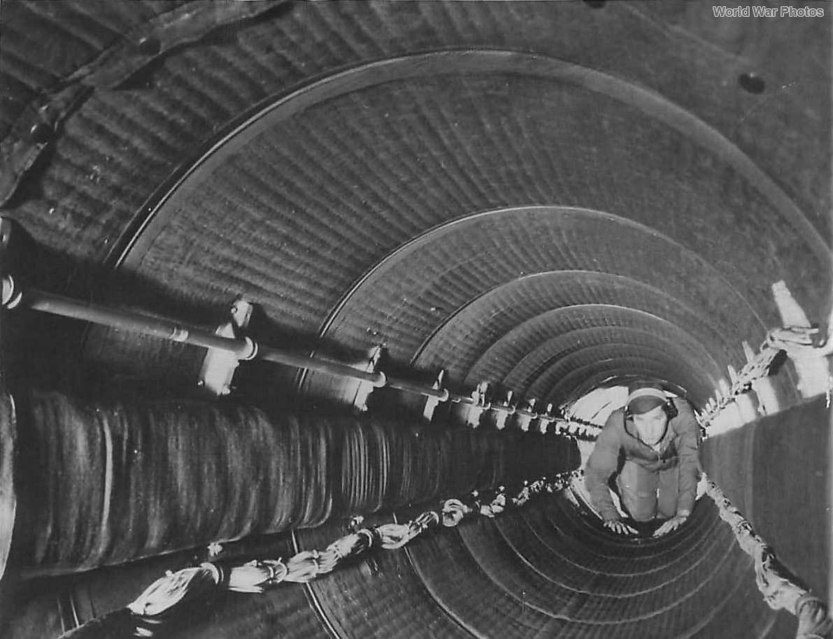 Crewman crawling thru padded fuselage tunnel of B-29