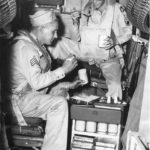 Crewmen dine from food tray galley aboard B-29