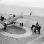 Grumman Wildcat fighter of No 882 Squadron Fleet Air Arm being manoeuvred into position for takeoff from HMS PURSUER off the northern coast of Norway