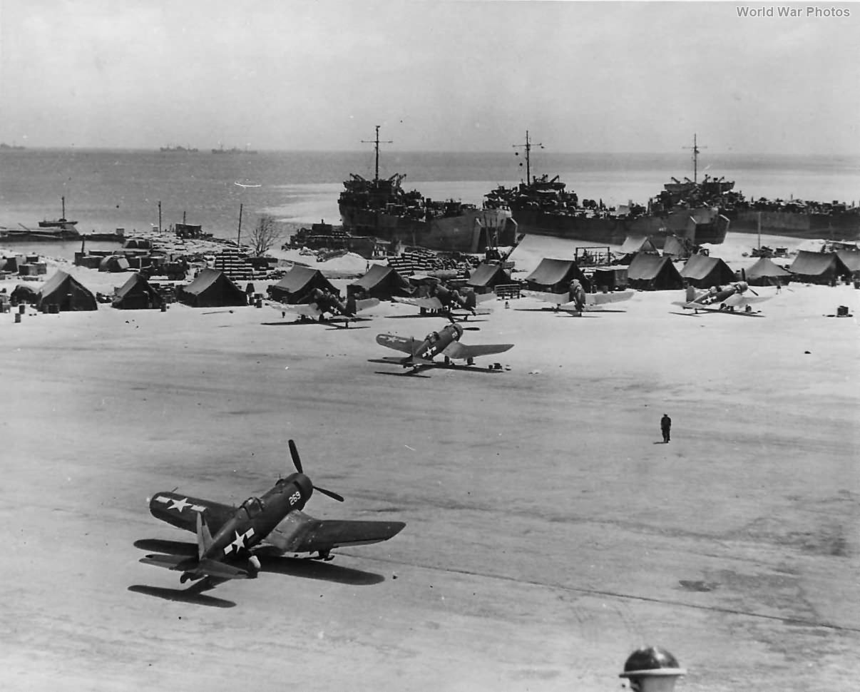 Corsairs on runway and LSTs on Beach at a Marshall Islands Base 1944