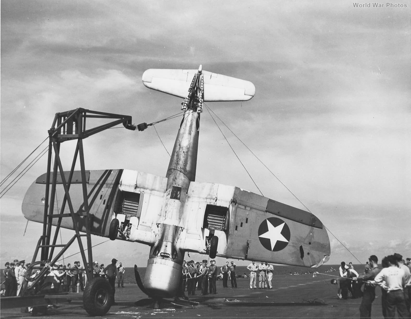 F4U-1 of VF-17 is being lifted from the deck of USS Bunker Hill