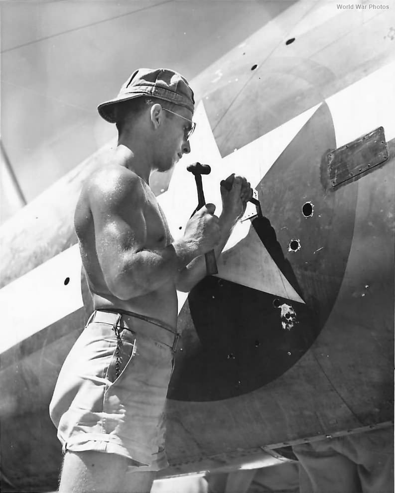 Marine mechanic patches bullet holes in F4U Bougainville 1944