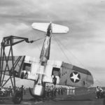F4U-1 VF-17 is being lifted from the deck of USS Bunker Hill