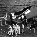 An Honor Guard carries the flag draped body of a shipmate from the deck elevator in preparation for a burial at sea on board the carrier Bataan CVL-29 1945