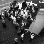 Flight deck personnel attend to a wounded pilot of VF-19. F6F-5 Hellcat #22 USS Lexington CV-16 – Battle of Leyte Gulf, October 24, 1944