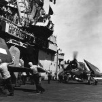 USS Essex CV-9 crew push F6F Hellcats of VF-15 forward 1944