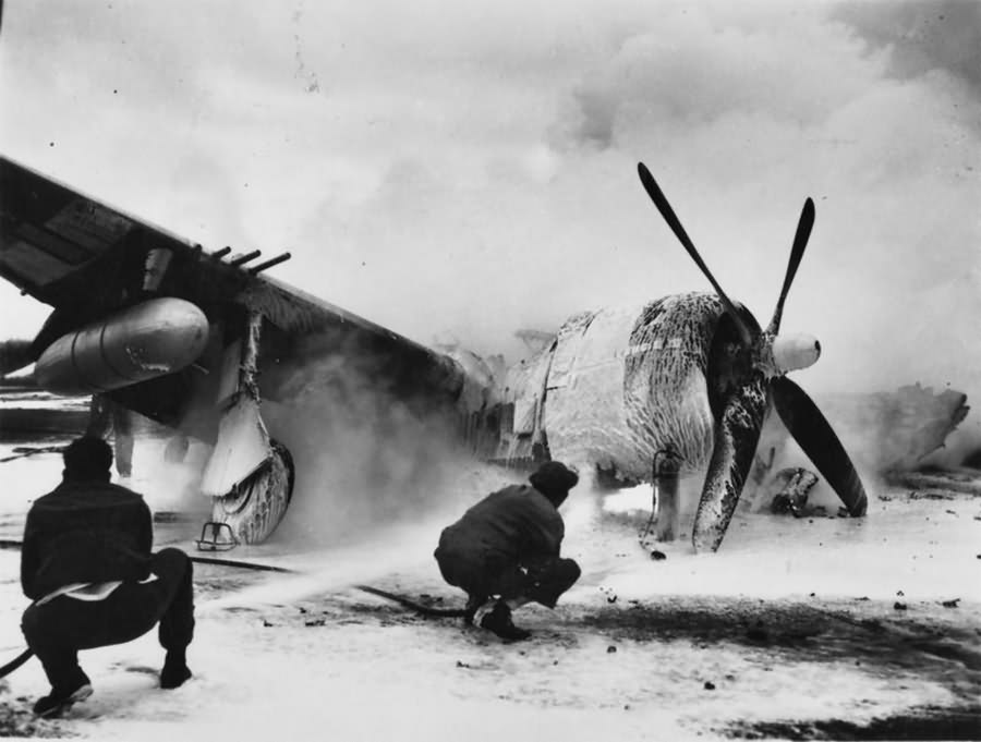 """Ground personnel of the 56th FG, extinguishing a burning P-47 HV-V 42-26300 """"Pengie III"""" – Boxted July 1944"""