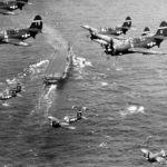 SB2C Helldivers and F4U in flight over aircraft carrier